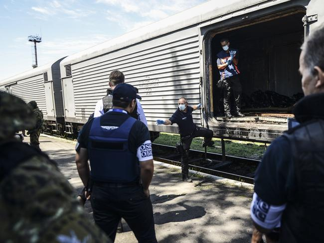 "Monitors from the Organization for Security and Cooperation in Europe (OSCE) and members of a forensic team inspect a refrigerator wagon containing the remains of victims from the downed Malaysia Airlines Flight MH17, at a railway station in the eastern Ukrainian town of Torez on July 21, 2014. The head of a Dutch forensic team said on Monday a train, carrying the remains of victims from the Malaysian airliner crash, should set off later on Monday to a place where ""we can do our work"" AFP PHOTO/ BULENT KILIC"