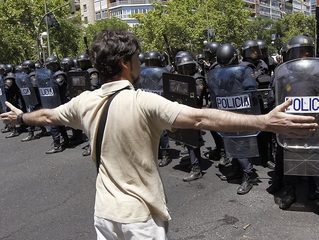 A man stands in front of riot policemen during a coal miners' demonstration in Madrid.