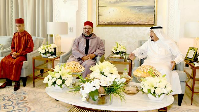 The Saudi king (right) did mix a little bit of business with pleasure, entertaining Morocco's King Mohammed VI (centre) at his holiday home. Picture: Moroccan Royal Palace
