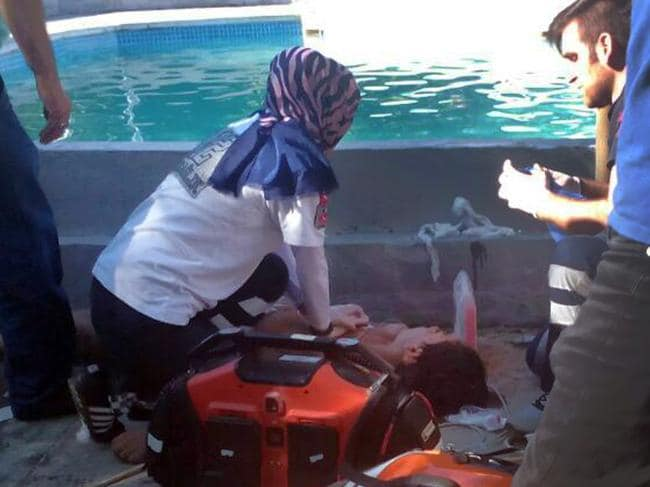 Medics assist a person who was electrocuted at a water park in the town of Akyazi, in Sakarya province, northwest Turkey, Friday, June 23, 2017.  Turkish media say five people have been electrocuted at a water park pool,  including two teens and a 12-year-old. The private Dogan news agency said Friday the three youngsters were caught up in an electrical current in the pool at the park. The park's manager and his son were killed when they dived into the pool to try and save the children.  (DHA-Depo Photos via AP)