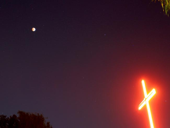 Night light ... a religious cross is seen as the moon shines down on Los Angeles, California. Picture: Getty