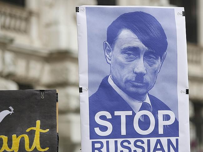 Comparisons ... activists hold a poster featuring Russian President Vladimir Putin as German Nazi dictator Adolf Hitler. Picture: Dieter Nagl