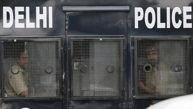 Indian policemen look out from a van carrying four men convicted in the fatal gang rape of a young woman on a moving New Delhi bus. (AP Photo/Manish Swarup)