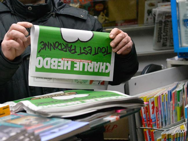Popular ... a man buys a copy of the new edition of Charlie Hebdo magazine at a Pigalle newsstand in Paris, France. Three million copies of the controversial magazine have been printed so far. Picture: Aurelien Meunier/Getty Images