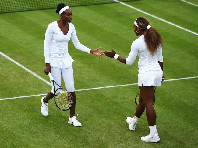 Venus Williams and Serena Williams touch hands between points in a doubles match at Wimbledon. That really pees McEnroe off.