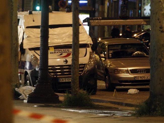 The car belonging to an attacker and a police van are pictured on the Champs Elysees in Paris.