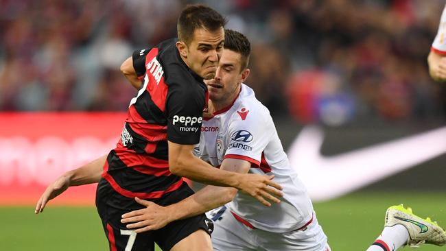 Steven Lustica of the Wanderers (left) is tackled by Adelaide United's Ben Warland.