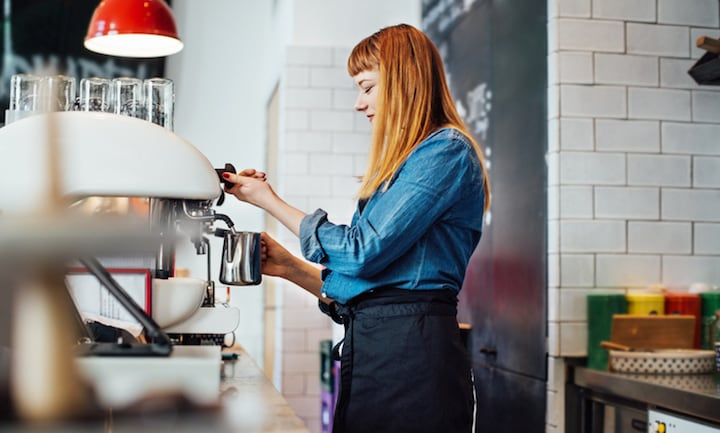 Side view of female barista steaming milk at cafe