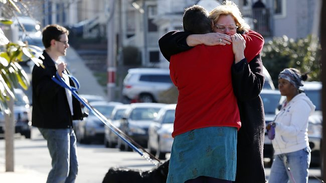 Neighbours hug outside the home of the Richard family in the Dorchester neighbourhood of Boston. Picture: Michael Dwyer