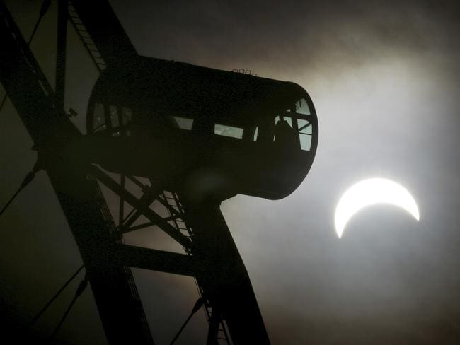 A partial solar eclipse is seen behind a passenger capsule of the Singapore Flyer in Singapore. Picture: AP