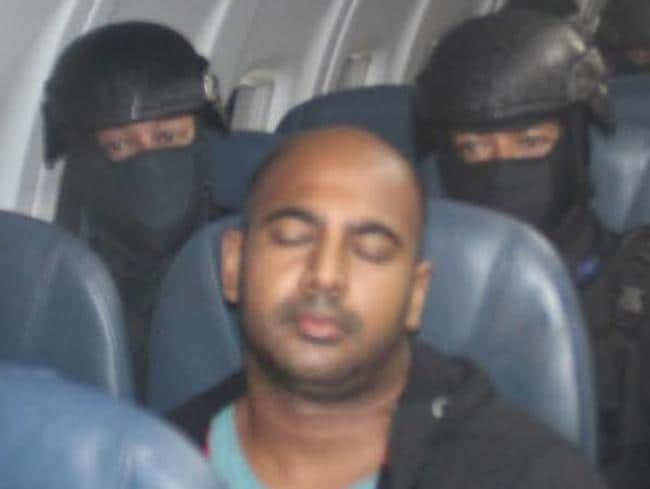 Armed guards ... Myuran Sukumaran sits on the plane to the prison island of Nusakambangan. Picture: Supplied