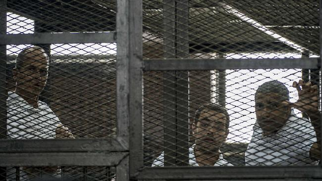 Awaiting their fate ... Peter Greste and his colleagues Baher Mohamed and Mohamed Fadel Fahmy listen to the verdict inside the defendants cage.