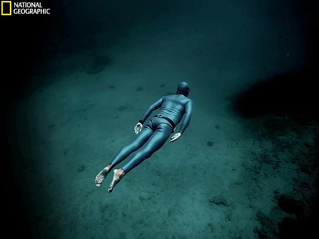 Freediver slides peacefully over sea bed in the blue hole area of Vouliagmeni.