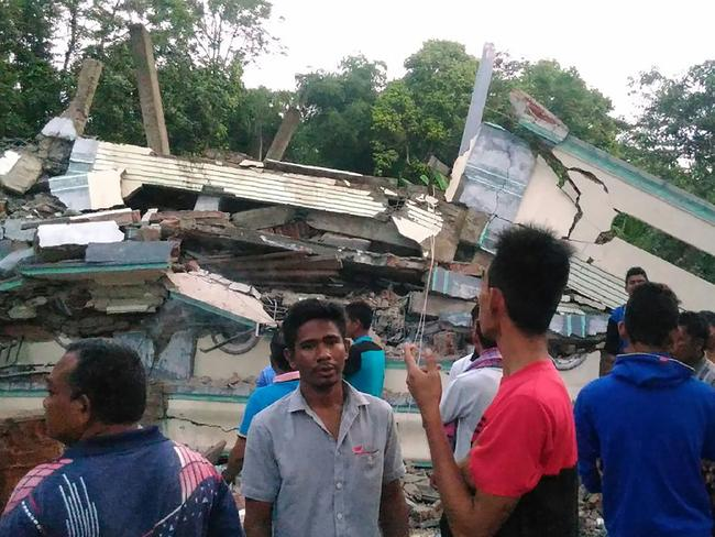 Residents gather around a collapsed building after the strong earthquake. Picture: Zian Muttaqien.