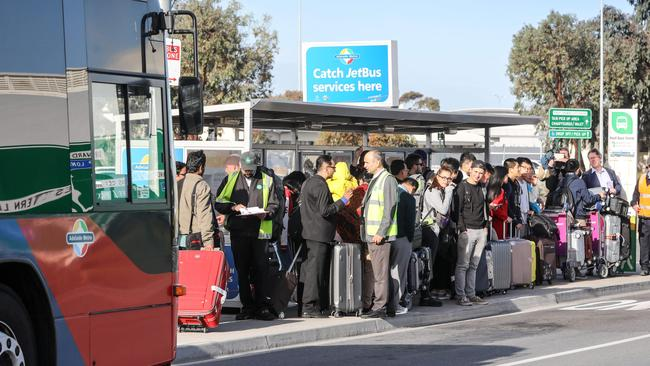 Arrivals waiting at the Adelaide Airport bus stop. Picture: Russell Millard/AAP