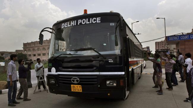 A police van leaves a court complex carrying four men convicted in the fatal gang rape of a young woman on a moving New Delhi bus in December last year. (AP Photo/Manish Swarup)