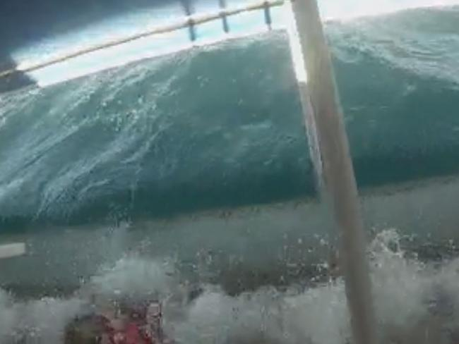 Tourists scream as they are engulfed by waves in the chilling footage.