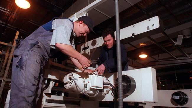 1996: Mark Gowdie and Rod Dalton fit a new ektacolor bulk paper slitter at the Kodak plant in Coburg. Picture: Herald Sun Image Library