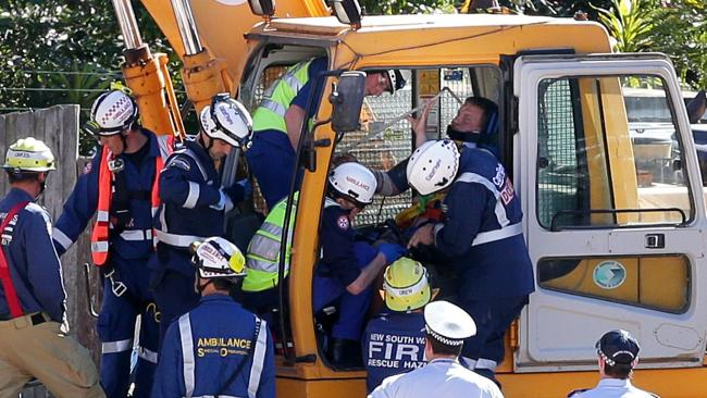Construction worker, Kieran, 19, is cut free from the excavator cabin before being transported to Royal North Shore Hospital. Picture: Adam Ward