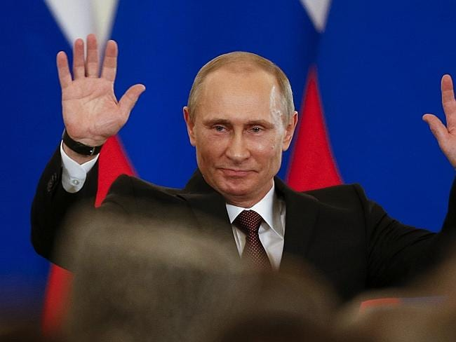 V for victor ... Russian President Vladimir Putin gestures after signing a treaty to incorporate Crimea into Russia in the Kremlin in Moscow. Picture: Alexander Zemlianichenko