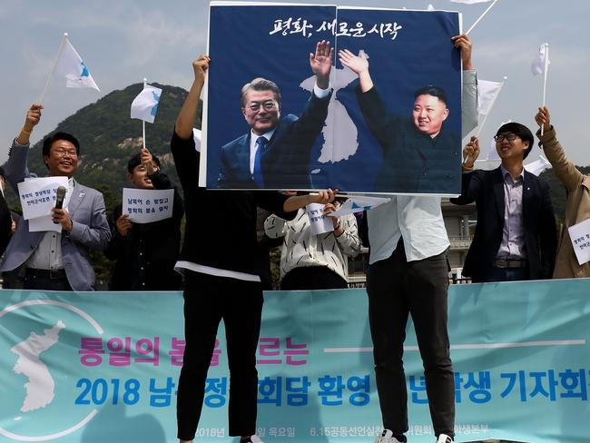 South Koreans hold up placards of South Korean President Moon Jae-In and North Korean leader Kim Jong-un during a rally welcoming the planned Inter Korean Summit. Picture: Getty