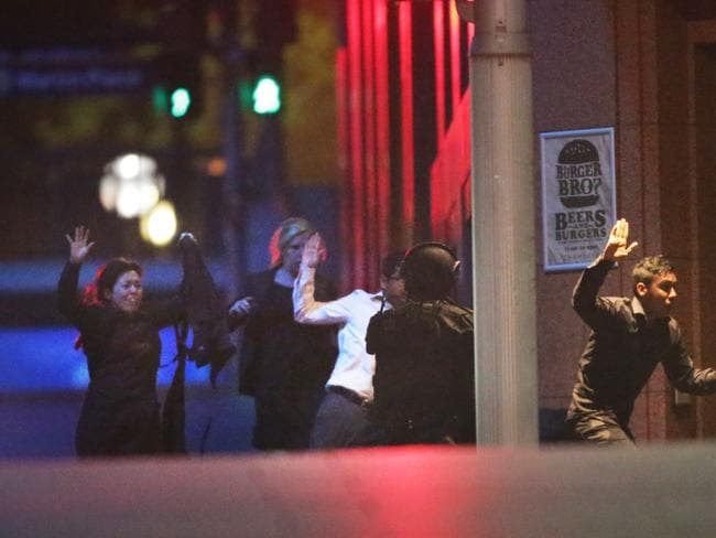 Terror ... Hostages flee the scene at the end of the 16-hour siege. Picture: Bill Hearne