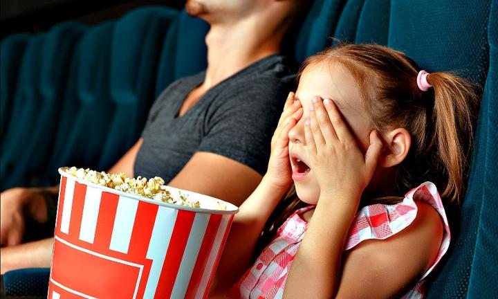 Little girl closing her eyes with hands at the cinema