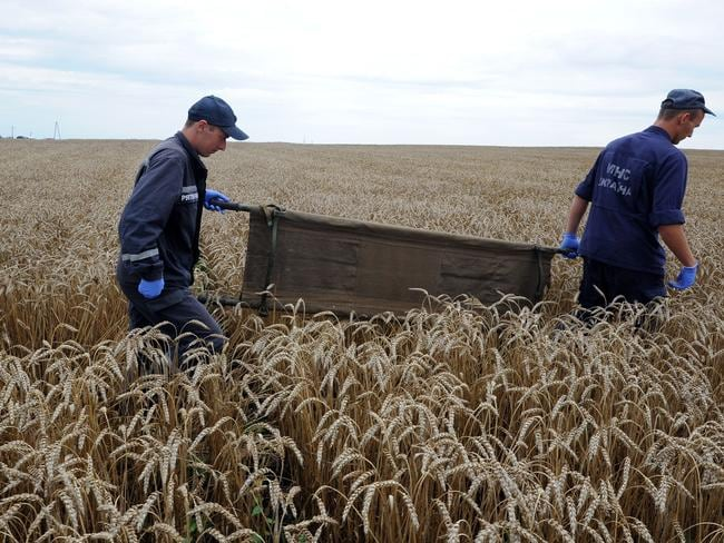 'Strewn over fields' ... Ukrainian rescue workers collect the bodies of victims at the crash site of a Malaysian jet. Picture: Dominique Faget