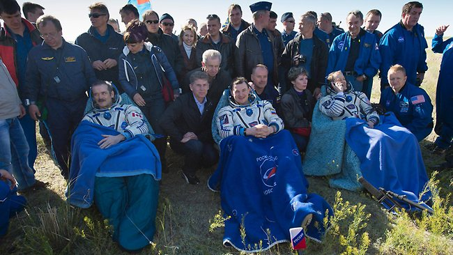 Expedition 35 Commander Chris Hadfield of the Canadian Space Agency (CSA), left, Russian Flight Engineer Roman Romanenko of the Russian Federal Space Agency (Roscosmos), centre, and NASA Flight Engineer Tom Marshburn sit in chairs outside the Soyuz Capsule just minutes after they landed in a remote area near the town of Dzhezkazgan, Kazakhstan. (Photo by Carla Cioffi/NASA via Getty Images)