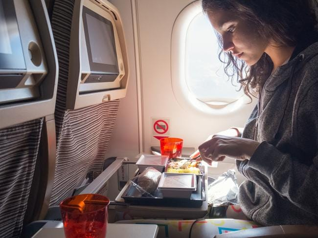 Young woman having lunch in airplane.  Plane food, Susie Burrell, Daily Escape
