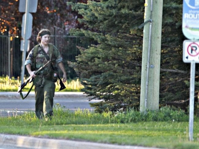 On the loose ... Justin Bourque walks on Hildegard Drive in Moncton, New Brunswick, on Wednesday, June 4, 2014, after several shots were fired in the area. Picture: AP/The Canadian Press, Moncton Times & Transcript, telegraphjournal.com, Viktor Pivovarov