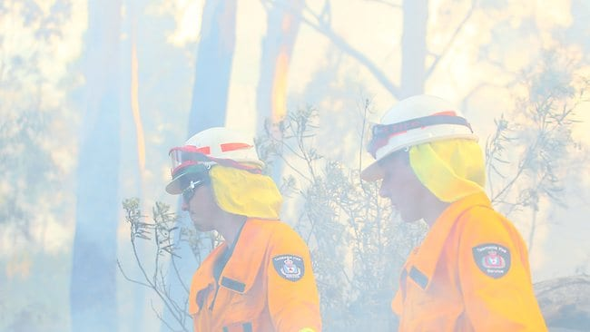 Ben Duggan (left) and Connor Robson in the thick of smoke putting out a bushfire in Glen Huon. Picture: Luke Bowden