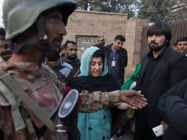 Worst nightmare ... a Pakistani army soldier clears the area outside a school attacked by Taliban in Peshawar as anxious parent wait for news of their children. Picture: AFP
