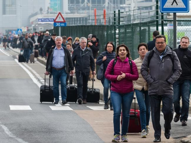 People walk away from Brussels airport after the explosions rocked the facility. Picture: AP / Geert Vanden Wijngaert