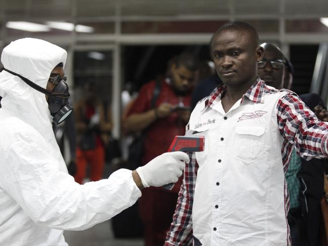 Health scans ... Nigerian port health official uses a thermometer on a worker at the arrivals hall of Murtala Muhammed International Airport in Lagos, Nigeria. Picture: AP