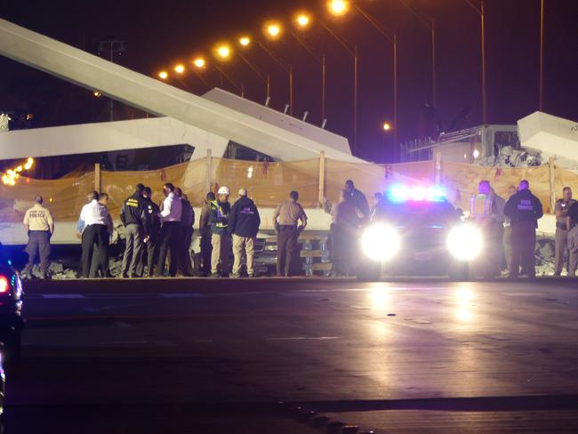 Police lights illuminate the scene of a pedestrian bridge collapse in Miami crushing a number of cars below. Picture: AFP