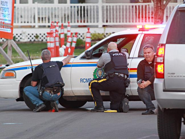Cop hater ... Police officers take cover behind vehicles in Moncton after Justin Bourque killed three colleagues and wounded two more.