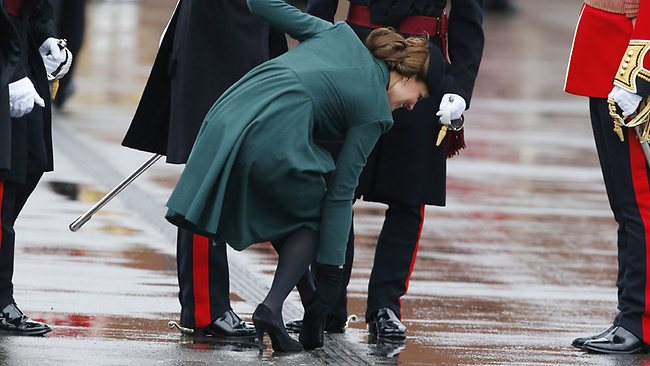 Britain's Kate Duchess of Cambridge holds onto her husband Prince William, left, as she bends down to pull the heel of her shoe out of a drainage grill it got stuck in, as she presents the traditional sprigs of shamrocks to members of the 1st Battalion Irish Guards at the St Patricks Day Parade at Mons Barracks in Aldershot, England, Sunday, March 17, 2013. Kate presenting the sprigs of shamrocks to the regiment Sunday, follows a century-old tradition inaugurated by Queen Alexandra, the wife of the then King, Edward VII back in 1901. (AP Photo/Matt Dunham)