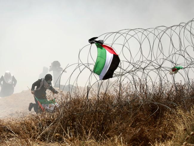 A Palestinian protester holding his national flag runs past barbed wires during clashes with Israeli forces near the border between the Gaza Strip and Israel east of Gaza City on May 14. Picture: AFP