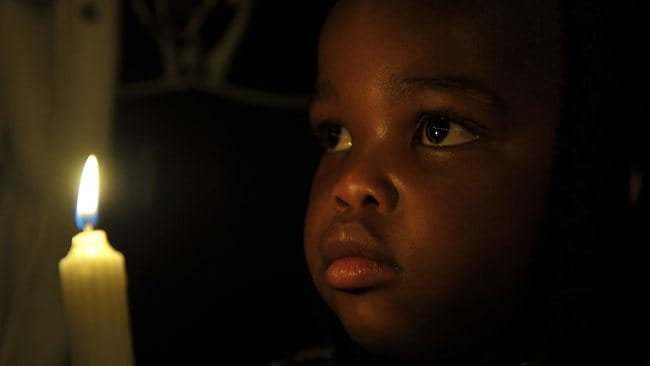 A child holds a candle as he prays for the recovery of Nelson Mandela outside the Mediclinic heart hospital in Pretoria.