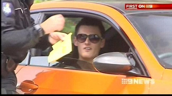 Bernard Tomic being booked in his orange BMW sport on the Gold Coast.