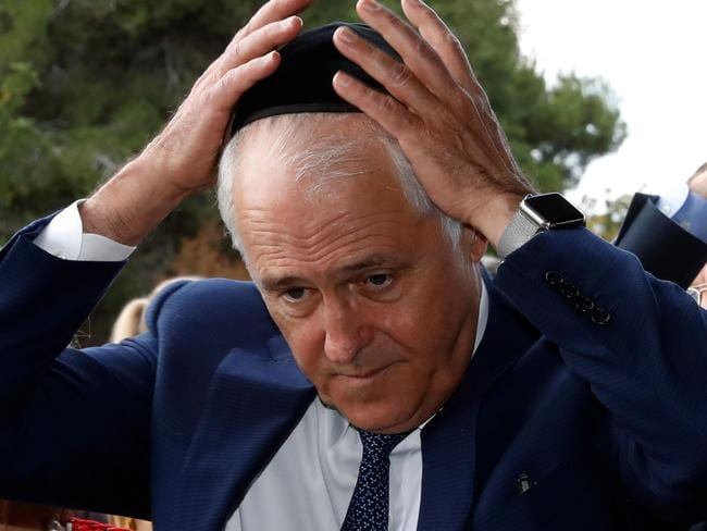 Malcolm Turnbull puts on a kippa as he visits the Yad Vashem Holocaust Memorial museum in Jerusalem commemorating the six million Jews killed by the Nazis during World War II. Picture: AFP/ Gali Tibbon