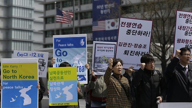 """South Korean protesters shout slogans during a rally denouncing the joint military exercises between South Korea and U.S. and demanding U.S. Secretary of State John Kerry go to North Korea for peace talks, near the U.S. Embassy in Seoul, South Korea, Friday, April 12, 2013. Kerry is traveling to Asia to meet with U.S. allies and visit here on the first leg of his three-nation Asian tour. The letters read """"Stop war exercises."""" (AP Photo/Lee Jin-man)"""
