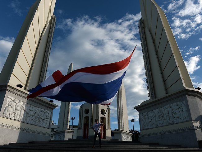 Symbolic gesture ... a man waves a giant national flag at Democracy Monument as the site of months of anti-government protests is cleaned up a day after the Thai army seized power in Bangkok.