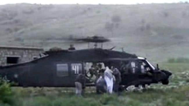 Leaving Afghanistan ... men in civilian clothing lead Sgt. Bowe Bergdahl, in white, towards a helicopter. Picture: Voice Of Jihad Website via AP video