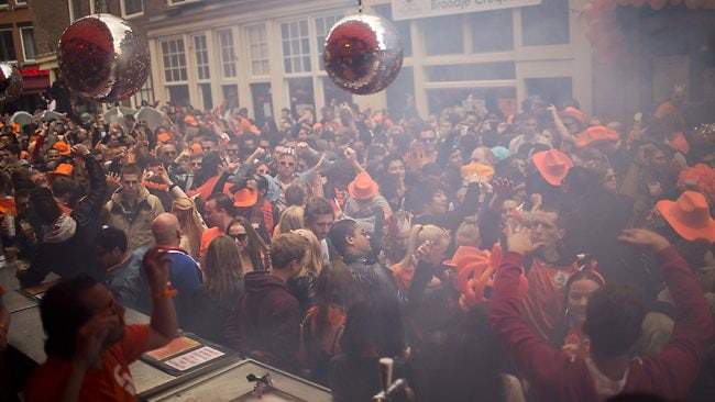 People dance In the street in Amsterdam, The Netherlands, Tuesday April 30, 2013. Around a million people are expected to descend on the Dutch capital for a huge street party to celebrate the first new Dutch monarch in 33 years. (AP Photo/Emilio Morenatti)