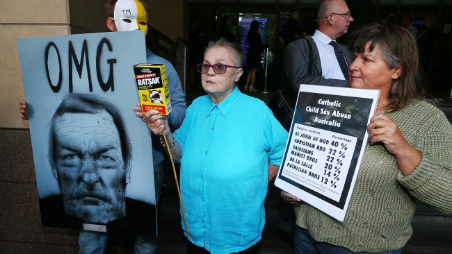 Protestors demonstrate after Cardinal George Pell arrives at Melbourne Magistrates' Court. Image: Getty.