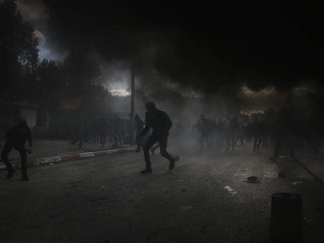 Smoke billows from burning tyres as Palestinian demonstrators clash with Israeli troops in Ramallah. Picture: in the Israeli-occupied West Bank on December 7, 2017. / AFP PHOTO / ABBAS MOMANI