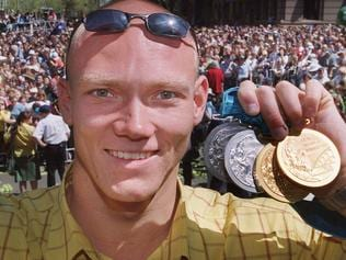 Swimmer Michael Klim showing Olympic gold and silver medals during ticker tape parade of Olympians through streets of Sydney after Olympic Games 03 Oct 2000. tickertape medal p/