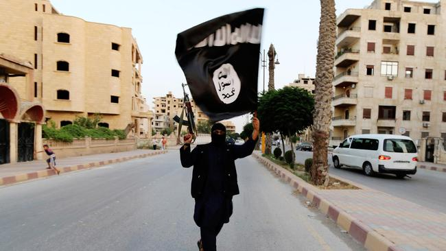 Defiant ... a member loyal to the Islamic State in Iraq and al-Sham waves a flag in Raqqa, Syria.